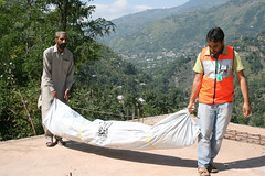 IR team memeber helps an affected person in moving a tent to his place.jpg