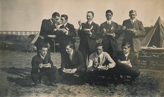 Group of men eating and feeding each other (simpleinsomnia) Tags: old railroad bridge camp food white black men monochrome vintage found outside blackwhite tents sand feeding eating antique snapshot tie suit photograph vernacular unusual railroadbridge foundphotograph suitandtie