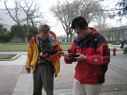 2 guys looking at cell phones testing a location-aware game