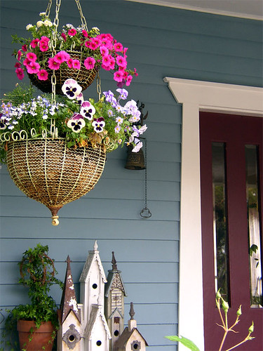 Front porch with hanging baskets and collection of birdhouses, via Flickr: liquidskyarts