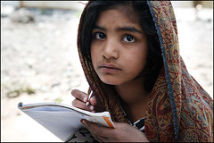 Schoolgirl - after the earthquake in Pakistan (Maciej Dakowicz) Tags: school pakistan camp people girl face pen pencil writing canon children photography eos earthquake education october ruins expression relief help 5d effort write kashmir journalism humanitarian ngo notepad theface balakot twtmeblogged