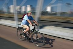 Hurry Home (krobbie) Tags: bridge motion hat bicycle rotterdam nikond70 random 1224mmf4g brug nophotoshop tracking erasmusbrug nops krobbie capturenx