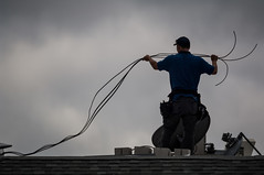 the cable guy (heavysoulclick) Tags: street urban man color guy rooftop hat cali comcast san francisco alone dish cable wires bayarea blocks cinder