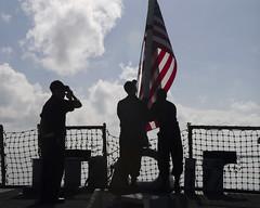 Sailors lower the ensign on the flight deck of USS John S. McCain.