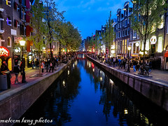 Amsterdam early on a saturday night (Malcom Lang) Tags: city blue trees red sky people streets reflection green water netherlands amsterdam yellow bar night buildings concrete lights canal cafe bricks saturday bikes casino bin busy walkway poles crowds canonpowershot malcomlang malcomlangphotos