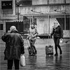 Rainy day travellers (John Riper) Tags: johnriper street photography straatfotografie square vierkant bw black white zwartwit mono monochrome netherlands candid john riper canon 6d 24105 l vlasmarkt young ladies women girls baggage luggage trolleys rain wet pavement man pigeons doves surprised