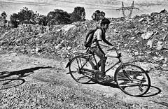 heading for the future (Greyframe) Tags: living life bangalore bangaluru urban poverty hard boy bike new trash landfill street black white waste dirt greyframe monochrome grey photography blackwhite blackandwhite bw blwh schwarz weiss schwarzweis people poor india indien trip einfarbig future hope young man