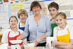 Cheap Games and Toys for Kids (cheapgamesandtoysforkids) Tags: school girls portrait food woman color colour boys students smiling horizontal standing children baking education classroom image tocamera class apron teacher demonstration indoors teen learning teenager teaching cheerful forties aprons helping 40s teenage cookery caucasian demonstrating homeeconomics middleaged secondaryschool preteens 13yearold cookinglesson 12yearold middleagedwoman cookingequipment atcamera domesticscience fivepeople preadolescents