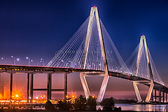 Ravenel Bridge from Waterfront Park (Jerry Fornarotto) Tags: city travel bridge blue sunset sky orange sc water yellow vertical architecture modern night river landscape outdoors photography lights evening pier twilight arch waterfront suspension dusk vibrant south mountpleasant scenic southcarolina engineering landmark structure diamond cables photograph transportation cooper carolina upright iconic charlestonsc suspensionbridge span architech fishingpier cooperriver ravenel lowcountry cooperriverbridge ravenelbridge cablestaybridge patriotspoint royalblue longexposeure newcooperriverbridge cablestay arthurravenelbridge diamondshape penulum jerryfornarotto