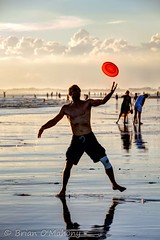 A Sense Of Freedom (Brian O'Mahony) Tags: red sea sky people bali cloud reflection beach water sport indonesia happy freedom jump sand joy catch frisbee seminyak canon70200mmf28l brianomahony thephotographiceye canon5dmarkii