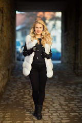 hallway (Michael Kremsler) Tags: shooting model jeans boots pullover fur vest blond woman bokeh portrait fashion streetfashion hallway availablelight evening city pavement stones wall