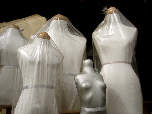 four plain white cotton mannequins in plastic bags with a small, silver mannequin