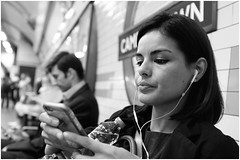 Plugged in (mesonparticle) Tags: bw woman london mobile lady phone camden cellphone mobilephone headphones fujifilm londonunderground camdentown thetube iphone appleiphone x100t topgunning