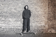 black and white shoot of a teenage boy with hoodie standing on a long board (Armin Staudt) Tags: street boy shadow urban man black male brick feet sport wall youth standing vintage dark freedom hoodie cool shoes waiting skateboarding pavement grunge young culture lifestyle teen skate trendy longboard figure skateboard teenager skater sullen skateboarder lean