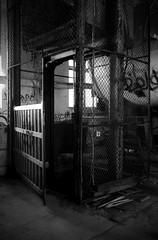 Claustrophobia (Wєirdlig) Tags: abandoned exploring exploration urbex rurex decay asbestos creepy abstract eclectic vacant photography destroyed urban ruins trespass trespassing haunted desolate architecture building house home colorado indoor interior blackandwhite monochrome bw elevator cage bars metal claustrophobia claustrophobic door gate grate grating light lighting mill factory