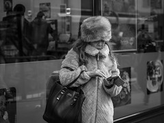 Meanwhile In Siberia... (Leanne Boulton) Tags: monochrome urban street candid portrait portraiture streetphotography candidstreetphotography candidportrait streetlife woman female face facial expression look emotion feeling fur furry coat hat winter cold weather mobile phone tone texture detail naturallight outdoor light shade city scene human life living humanity people society culture fashion canon5d canon 5dmarkiii character 70mm ef2470mmf28liiusm black white blackwhite bw mono blackandwhite glasgow scotland uk