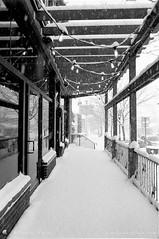 Film Photography: Snowed In Mangia Ristorante Porch, Orchard Park, NY (NFE_0059) (masinka) Tags: mangia ristorante orchardpark ny newyork film analog blackandwhite bw monochrome fe nikon ilford delta 100 xtol winter snow snowfall snowstorm porch fourcorners wny 716 etbtsy restaurant suburb buffalo