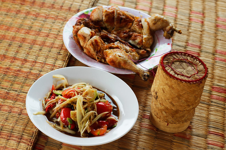 Som Tam, bbq chicken and sticky rice is a popular Isan meal
