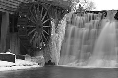 Dells Mill's Wheel & Falls (Leviathor) Tags: winter blackandwhite bw white black mill water wisconsin waterfall interestingness pond bravo augusta hdr highdynamicrange merge dells clarks 1740l 123bw