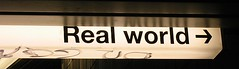 a sign with the words 'real world' followed by an arrow pointing to the right