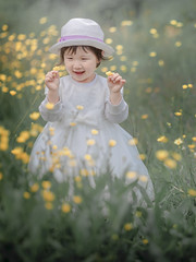 Jessie 01 (michaelinvan) Tags: toddler girl child spring whitegown hat flower yellow green grass face smile hands portrait natual light canon 5d2 135mm f2 richmond vancouver availablelight primelens cheerful plant buttercup