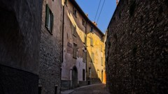 A diagonal of sunlight (Steve Brewer Photos) Tags: bergamo italy architecture sunlight street walls yellow windows lombardy northitaly cobbles cobblestones wideangle stonework shadow shade chiaroscuro city cityscape cittaalta citta townscape