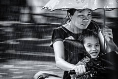 Happy in the rain (Axel Halbgebauer) Tags: laos luangprabang motorcycle kid bw blackandwhite blackwhite street sony sonyalpha streetphotography sonyimages streetportait southeastasia candid motion rain monsoon people face sonya6300