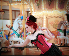Carousel (Kelly McCarthy Photography) Tags: woman model beautiful beauty fashion style glamour redhead redhair tophat minitophat corset skirt choker cameo necklace bokeh indoors carousel horse horses pose pink catchycolorspink magenta red purple yellow catchycolorsyellow ornate victorian gothic