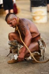 Doodling (naturalturn) Tags: renaissance fair faire renaissancefair renaissancefaire man costume furry tattoo leash loincloth california usa image:rating=4 image:id=212647
