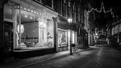 Late Night Shopping (McQuaide Photography) Tags: haarlem noordholland northholland netherlands nederland holland dutch europe sony a7rii ilce7rm2 alpha mirrorless 1635mm sonyzeiss zeiss variotessar fullframe mcquaidephotography lightroom adobe photoshop tripod manfrotto night nacht nightphotography stad city urban lowlight architecture outdoor outside illuminated street straat warmoesstraat window wideangle wideanglelens groothoek building longexposure oldstreet old oud character traditional authentic streetlight atmosphere sfeer christmas kerst winter emptystreet deserted empty nopeople cobblestone cobbles shadow light licht shop winkel shopfront shopwindow 169 blackandwhite mono monochrome bw