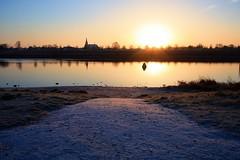Sunrise over the calm morning river (M a u r i c e) Tags: winter efs1022mm wideangle ultrawidezoom snow river maas grubbenvorst velden church netherlands sunlight sun sunshine sunrise water reflections light