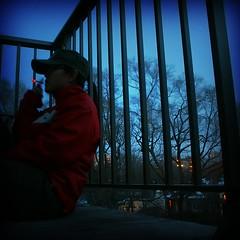 a break from being a bit bored (Lexcelsior ) Tags: blue trees home me lights glasses dusk cigarette balcony alexia free smoking jacket cap railing lex fauxlomo lexinthecity createandconquer 18sexposure notcoldouttonight