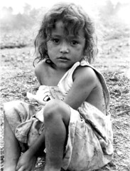 Nicaragua: Champigny (Laura Dunn-Mark) Tags: 2001 travel portrait blackandwhite bw film latinamerica girl youth kid waiting sitting child serious expression refugee innocent young photojournalism scan latinoamerica nicaragua etsy humanrights centralamerica nicaraguan jalapa bwportraits nuevasegovia lauradunnmark hurricanemitch