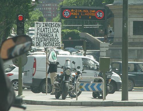 Un «ojo andante» en el Paseo de la Castellana de Madrid, denunciando la estafa de los sellos, y de paso  a notarios y a testaferros… WTF!?