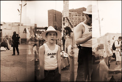 daddy jr. (pixietart) Tags: nyc boy bw film hat nycpb sepia brooklyn coneyisland costume holga police cigar plastic gothamist projects mermaidparade cyclone panarama seamonkey astroland revol mermaidparade2006 daddyjr