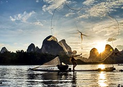 Cormorant fisherman casting his net, Xingping, Guilin (tehi75) Tags: china sunset nature asian liriver fisherman lowlight shadows guilin chinese culture silhouettes cormorant xingping castingnet catchingfish