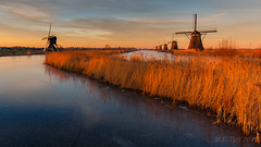 Warm winter sunset @ Kinderdijk (Marcel Tuit | www.marceltuit.nl) Tags: 1635 6d alblasserwaard boezem canon eos holland kinderdijk landscape landschap me marceltuit molen nederland thenetherlands unesco worldheritage color contactmarceltuitnl depth diepte goldenhour goudenuur ice ijs kleur landmark lucht moeras reed reflectie riet schemering sky sunset swam twilight warm water werelderfgoed windmill winter wwwmarceltuitnl zonsondergang mindfuck