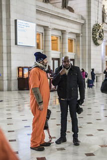 Abe Velazquez Speaks to a Curious Onlooker During an Anti-Torture Demonstration at Union Station