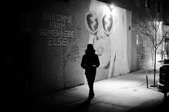 from somewhere else... (jeff_tidwell) Tags: street streetphotography streetphoto candid night graffiti art wall light shadows blackandwhite