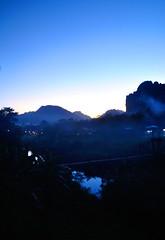 Vang Vieng (makingacross) Tags: laos pdr nikon d3000 vang vieng vangvieng mountains sky trees smoke evening blue nam song river namsong