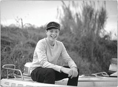 He Only Cares about Fixing His Boat (Steve Lundqvist) Tags: face bw black white bianco nero fashion menswear model young youth boy man hat cap beanie newsboy advertising boat barca sailor marinaio sea port porto sweater smile sorriso ragazzo gioventù portrait ritratto italians