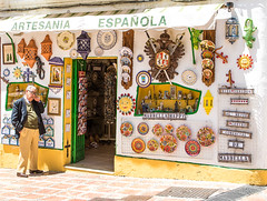 Shop keeper (JKmedia) Tags: spain spanish culture architecture style yellow white boultonphotography canoneos7dmarkii abroad shop plates souvenirs española shopkeeper man smartly dressed sunny warm artesaníaespañola candid n15c spectacles glasses marbella oldtown colourful ornamental sign signs gecko wall decoration