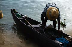 Fisherman at work. (bijindask) Tags: sea india lake plant black colour tourism beach water hat photography boat wooden fisherman ripple traditional small paddle wave kerala cleaning kochi 2014 fortkochi
