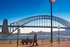 Walk By The Harbour Bridge (k009034) Tags: 500px water australia new south wales outdoors sydney travel destinations architecture beautiful bench buildings couple flags harbour bridge iconic lamp post landmark landscape oceania place see rail river sitting sky walking teamcanon