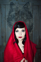Red Riding Hood (1950chick) Tags: selfportrait girl fairytale vintage wolf retro redlips blackhair bluedoor redridinghood wolfeyes photodesign redcape colorcontrast fairytalephotography
