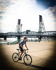 A Sunday Bike Ride (TMimages PDX) Tags: city bridge boy people urban usa bicycle river geotagged photography photo cityscape waterfront image streetphotography explore photograph hawthornebridge portlandoregon vignette fineartphotography tommccallwaterfrontpark flickrexplore explored iphoneography