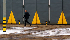 Beware of triangles! (jolanta mazur) Tags: candid street streetphotography geometry triangle pattern repetition tramdepot trambarn winter snow man maninblack sinister yellow black blackandyellow triangular warning warningsign unposed