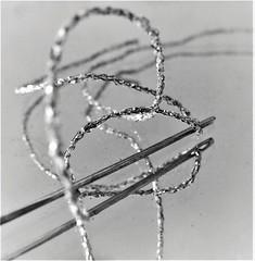 sparkle tangle HMM! (jenbrasnett) Tags: macromondays bw make me smile texturesandpatterns glitter thread needle loops curves monochrome sparkle reflection