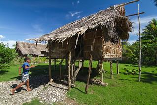 A boy runs towards his house, One' Oneabu village, Malaita Province, Solomon Islands. Photo by Filip Milovac.