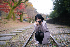 Young woman smiley taking pictures on dead railroad track (Apricot Cafe) Tags: 20s asianethnicity japan japaneseethnicity kyoto minikyoto2016 sigma35mmf14dghsmart autumn autumnleaves beautyinnature camera change charming cheerful enjoying foliage freshness happiness hope japanesefallfoliage japanesemaple leaves mapleleaf nature oneperson onlywomen outdoors people railroadtrack refreshing selectivefocus takingpictures tranquility traveldestinations walking wishing woman youngadult
